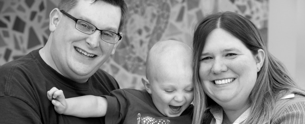 A family with a little toddler boy, smiling at the camera