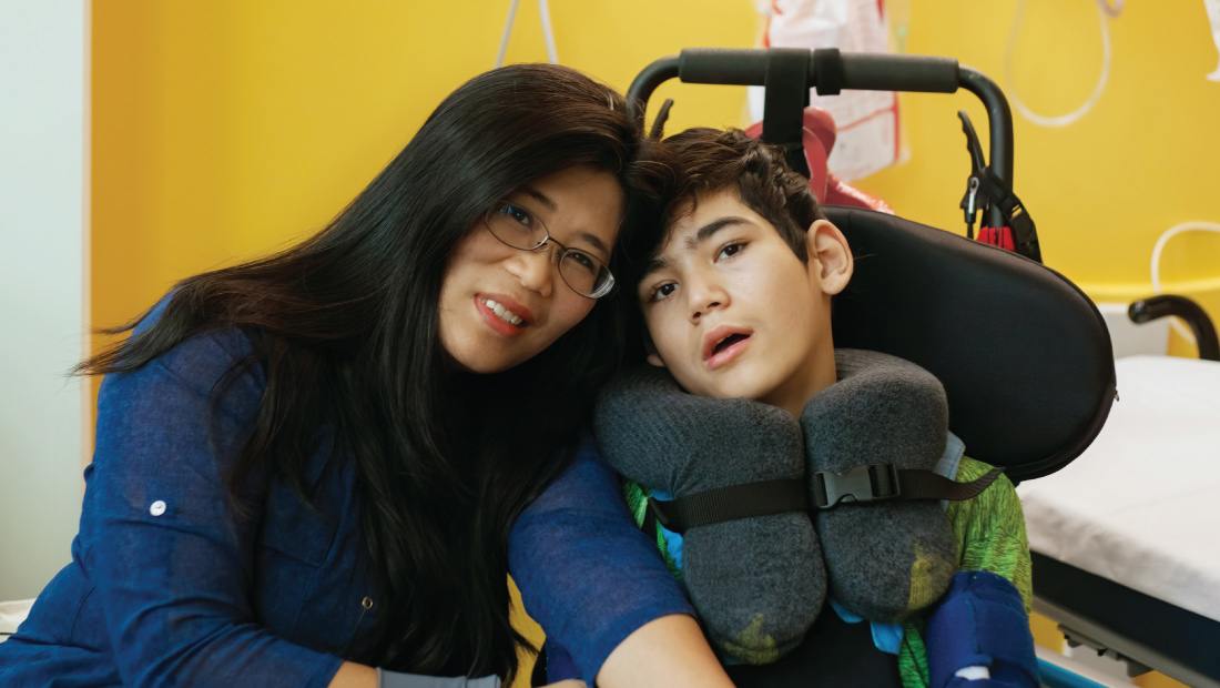 asian mother and special needs son together in hospital room
